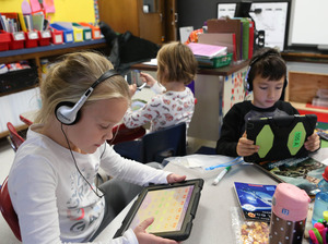 students working independently with headphones on